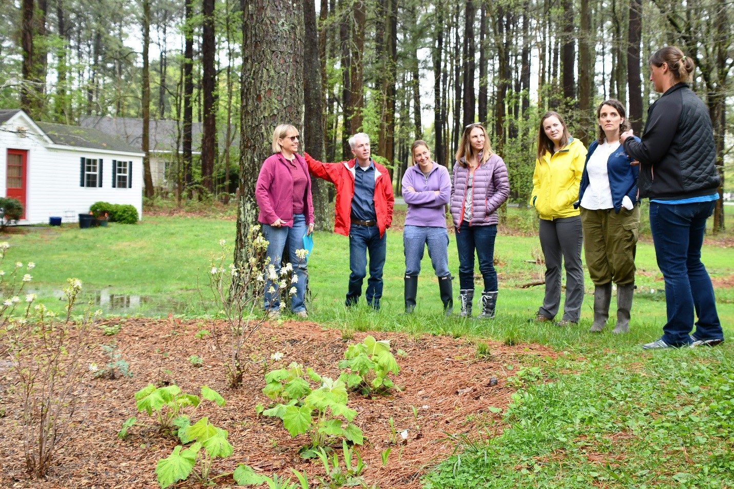 Landowner Assistance Coordinator Nicole Barth (far right) explains some of the features of Janet's (far left) rain garden to visitors. Plants were beginning to emerge on the early spring day.
